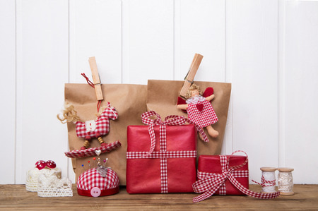 Christmas gift boxes wripped in paper bags with red white checked ribbon, angel, rocking horse and sewing supplies.