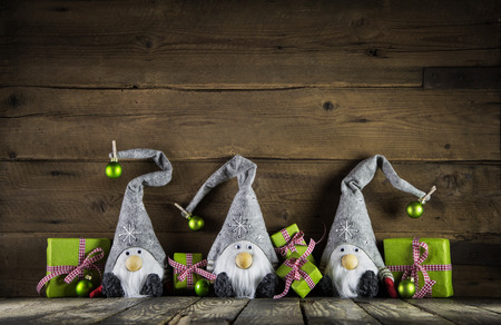 Three santa with grey felt hats and apple green christmas presents on an old wooden background for decoration.