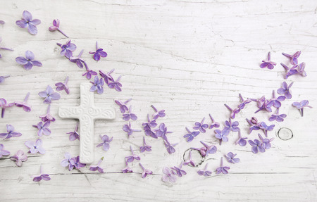 Cross and violet or purple lilac blossom on old wooden shabby background for a condolence card.