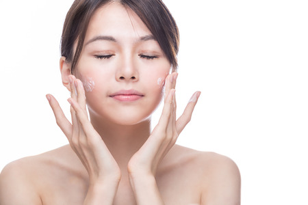 Chinese woman applying cream to face, skincare concept