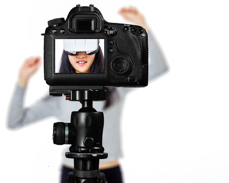 Photo for Focus on live view on camera on tripod, teenage girl  using VR goggles image on back screen with blurred scene in background. Teenage vlogger livestreaming show concept - Royalty Free Image