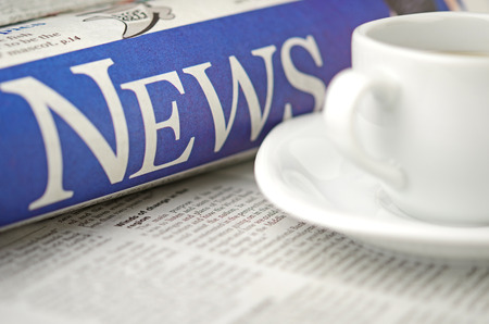 Newspaper and coffee cup macro shot with shallow depth of field