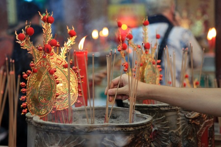 BANGKOK - JANUARY 23 : Chinese New Year 2012 - Man places incense stick in temple in Chinatown, Bangkok, Thailand on 23rd January 2012