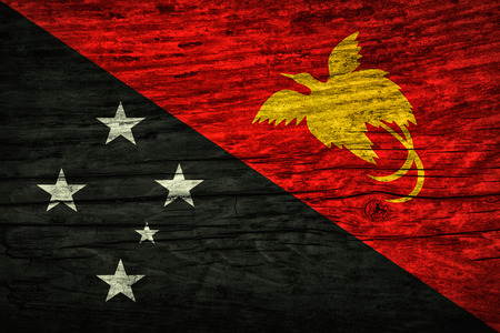The national vintage flag of Papua New Guinea on wooden surface