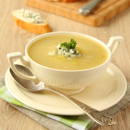 Homemade onion soup with celery and blue cheese on wooden background