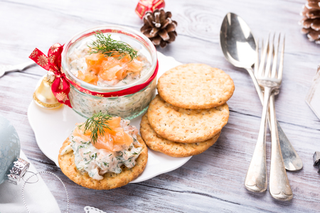 Foto de Smoked salmon, soft cheese and dill spread, mousse, pate, rillette in a jar with crackers on white wooden background. Delicious Christmas themed dinner table. Holiday concept. - Imagen libre de derechos