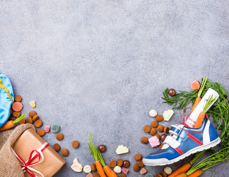 Dutch holiday Sinterklaas background with childrens shoe with carrots for Santas horse, pepernoten and sweets with copy space. Top view.