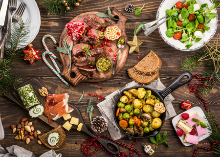 Foto de Flat lay of Delicious Christmas themed dinner table with roasted meat steak, appetizers and desserts. Top view. Holiday concept. - Imagen libre de derechos