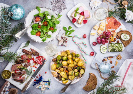 Photo pour Flat lay of delicious Christmas themed dinner table with roasted meat steak, appetizers and desserts. Top view. Holiday concept. - image libre de droit