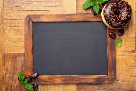 Photo for Black chalkboard with chocolate glazed donut - Royalty Free Image