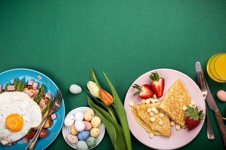 Photo for Easter composition with breakfast flat lay with scrambled eggs bagels, tulips, pancakes, bread toast with fried egg and green asparagus, colored quail eggs. Top view. Copy space. - Royalty Free Image