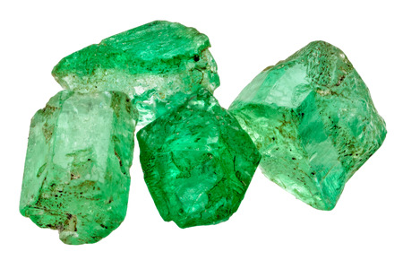 Four rich green emerald crystals on white