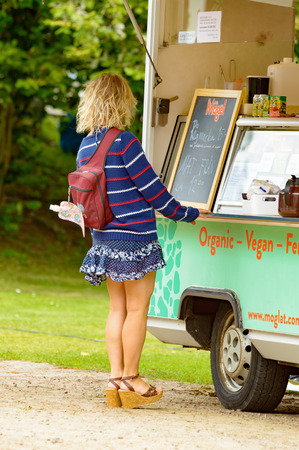 Smaland, Sweden - July 24, 2015: Attractive unknown woman stand in front of fast food wagon to purchase some food. She is wearing a short skirt, a sweater and heels, back towards you.