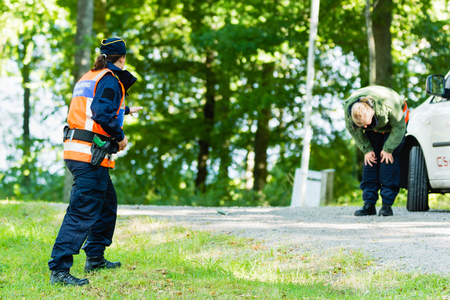 Vaxjo, Sweden - September 09, 2015: Police education. Outdoor weapons and apprehension training in public area. Pretending criminal has just been sprayed by pepper spray and bend down hurting.