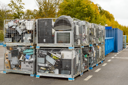 Netted bins full of discarded electronics waste waiting to be transported to the recycle plant for further processing. Blue containers in background.