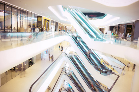 Photo pour People in motion in escalators at the modern shopping mall. - image libre de droit