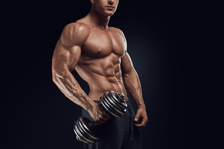 Foto de Handsome power athletic man with dumbbell confidently looking forward. Strong bodybuilder with six pack perfect abs shoulders biceps triceps and chest - Imagen libre de derechos