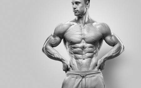 Photo pour Handsome power athletic young man with great physique. Strong bodybuilder with six pack perfect abs shoulders biceps triceps and chest. Studio shot on white background - image libre de droit