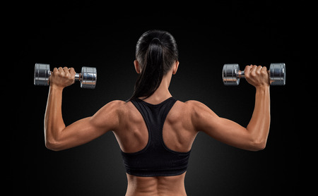 Fitness sporty woman in training pumping up muscles of the back and hands with dumbbells