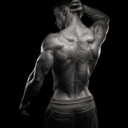 Handsome power athletic man turned back. Isolated over black background. Strong bodybuilder with shoulders, biceps, triceps and chest