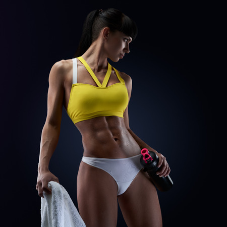 Photo for Fitness woman showing her abs, holding protein shake bottle ready for drinking. Close up of young woman's torso. Perfect abdomen muscles of a female athlete on black background. - Royalty Free Image