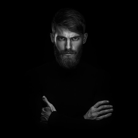 Photo for Black and white portrait of serious young man with folded and crossing hands standing Isolated on black background and looking at camera Confident concept - Royalty Free Image