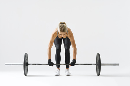Foto de Fitness attractive woman preparing to practice deadlift with heavy weights Female bodybuilder doing heavy weight lifting work out on white background Horizontal picture - Imagen libre de derechos