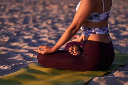 Young sporty woman practicing yoga by the sea, Lotus pose with mudra gesture, working out, wearing sportswear, pants and top, outdoor close up. Happiness concept Nature background.