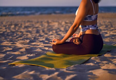 Young sporty woman practicing yoga, Lotus pose with mudra gesture, working out, wearing sportswear, outdoor close up. Happiness concept A woman is meditating alone at sunset. Nature background.