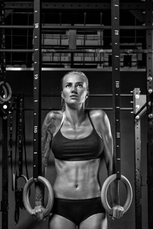 Photo for Female crossfit caucasian athlete in black sportswear exercising on gymnastic rings at gym Exercising woman holding gymnast rings and looking up. Workout at gym. Black and white photo. - Royalty Free Image