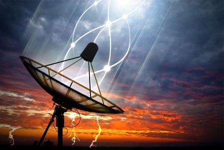 Black satellite transfer data under storm clouds