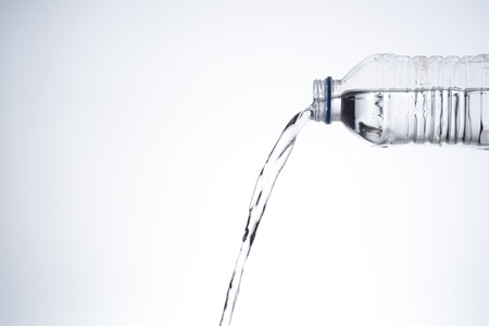 Pouring water from a plastic bottle, over white background