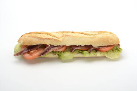 Foto de Anchovy sandwich with tomato and lettuce on white background - Imagen libre de derechos