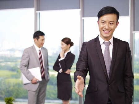 young confident asian business executive reaching out for a handshake