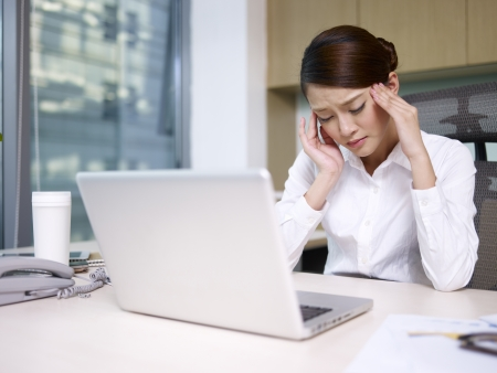 asian businesswoman sitting and thinking in office, looking tired