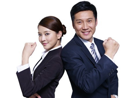 asian businessman and businesswoman standing back to back, making a fist