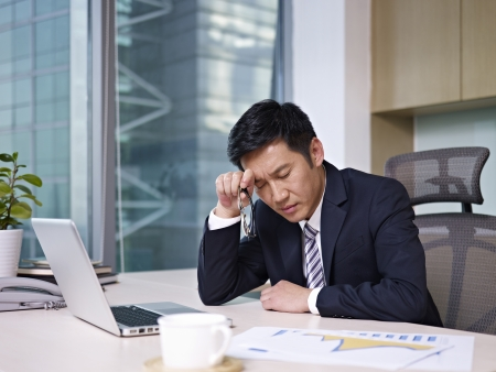 asian businessman sitting in office, looking tiredの写真素材