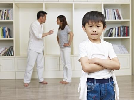 Photo pour 6-year old asian boy with quarreling parents in background  - image libre de droit