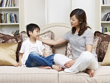 Photo pour asian mother and son having a conversation on couch at home - image libre de droit
