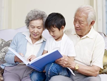 Photo pour grandparents and grandson reading a book together  - image libre de droit