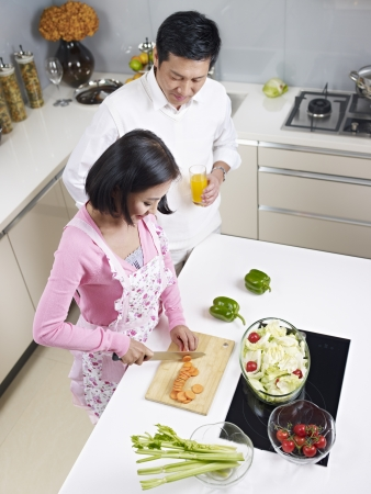 asian couple preparing meal together in kitchen