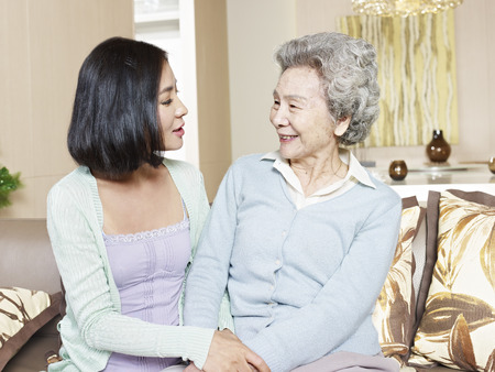 Foto de senior asian mother chatting with adult daughter at home - Imagen libre de derechos