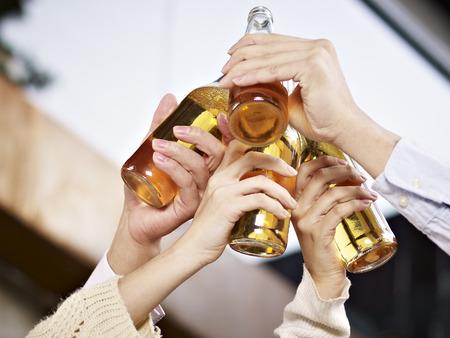 Photo pour beer bottles raised for a toast  - image libre de droit