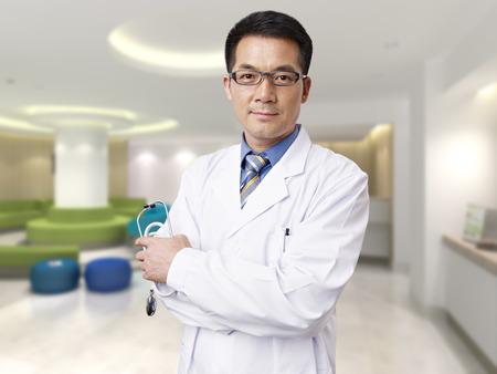 Photo pour portrait of a male asian doctor in hospital lobby. - image libre de droit