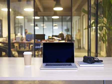 laptop computer, camera, coffee on top of a table in a modern, stylish office of a small business.