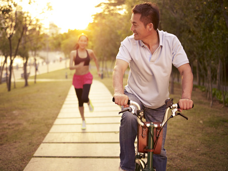 Photo pour young asian couple running, riding bike outdoors in park at sunset, fitness, sport and exercise, healthy life and lifestyle concept. - image libre de droit