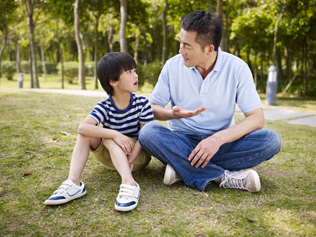 Photo pour asian father and elementary-age son sitting on grass outdoors having a serious conversation. - image libre de droit