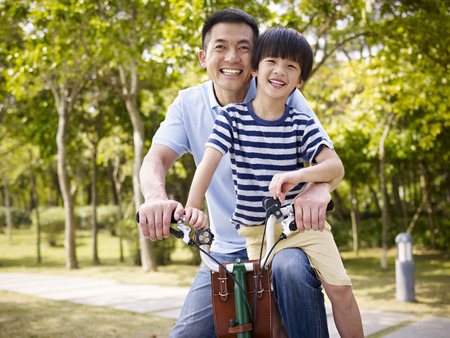 Photo pour asian father and elementary-age son enjoying riding a bike outdoors in a park. - image libre de droit