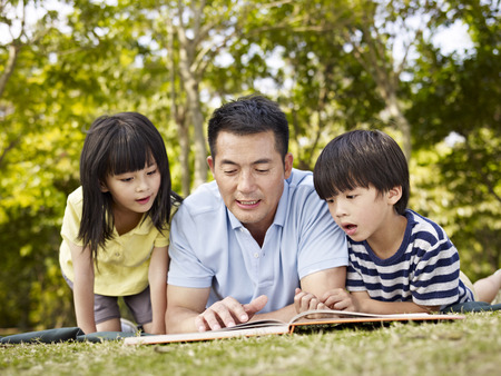 Photo pour asian father and children lying on grass reading a book together in a park. - image libre de droit