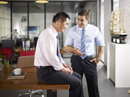 Photo pour asian and caucasian businessmen enjoying a pleasant conversation in office of a multinational company. - image libre de droit